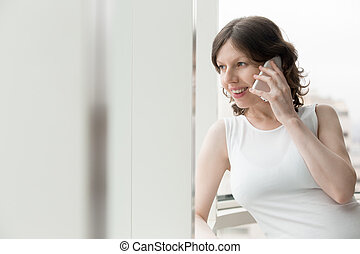 Happy woman talking on phone indoors