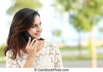Happy woman talking on phone looking away