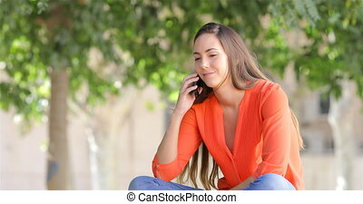 Happy woman talking on phone sitting in a park