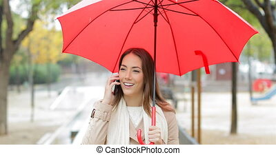 Happy woman talking on phone under the rain - Front view...