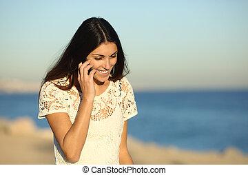 Happy woman talking on phone walking on the beach