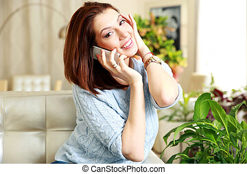 Happy woman talking on the phone at home
