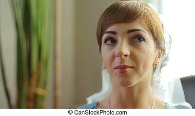 Happy woman talking to camera sitting on sofa