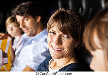 Happy Woman Talking To Daughter While Watching Movie In Theater