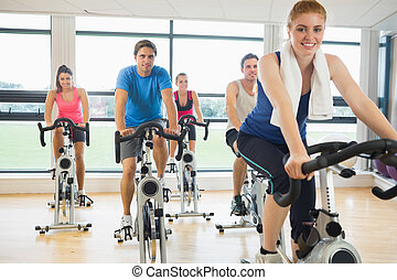 Happy woman teaches spinning class to four people - Portrait...