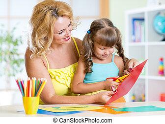 Happy woman teaching preschooler kid do craft items in daycare center