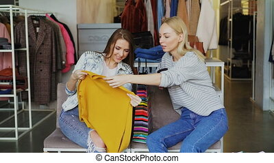 Happy woman telling her friend about purchased jumper, then...
