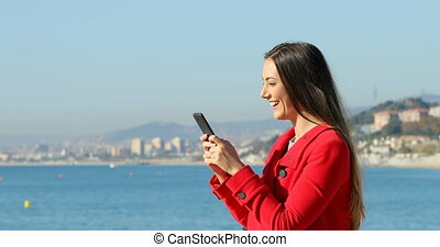 Happy woman texting on phone on the beach in winter