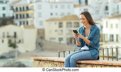Happy woman texting on phone outdoors on a ledge