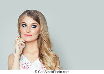 Happy woman thinking and looking up on white wall background with copy space