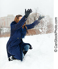 Happy woman throwing snow