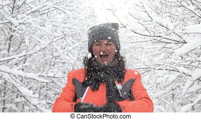 happy woman throwing up snow in winter park, having fun