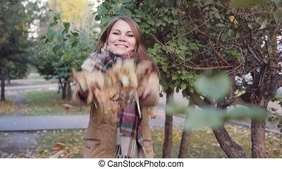 Happy woman throws autumn leaves in the autumn park in slowmotion. 1920x1080