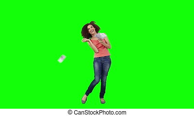 Happy young woman throws money away in front of a green background