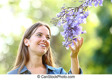 Happy woman touching flowers in a park