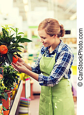 happy woman touching mandarin tree in greenhouse