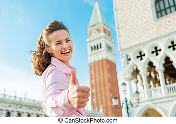 Happy woman tourist giving thumbs up on St. Mark's Square