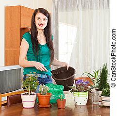 Happy woman transplanting flowers