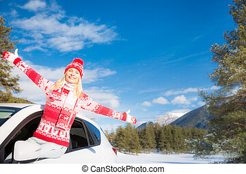 Happy woman travel by car in winter - Happy young woman...