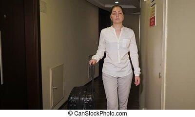 Happy woman traveler is walking on hotel corridor with...