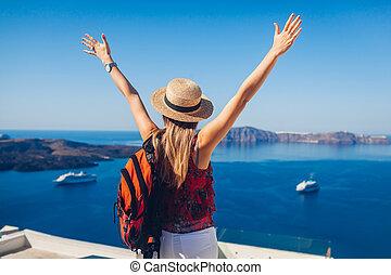 Happy woman traveler walking raising hands in Thera, Santorini island, Greece enjoying sea landscape. Summer vacation
