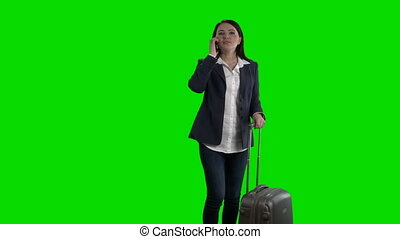 Happy woman traveling with suitcase waving her hand against green screen