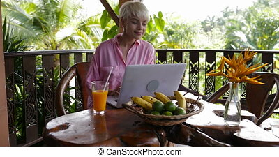 Happy Woman Typing On Laptop During Breakfast On Summer...