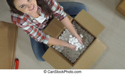 Happy woman unpacks moving cardboard box or parcel throwing foam chips in air