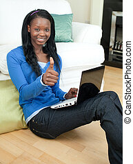 Happy woman using a laptop sitting on the floor