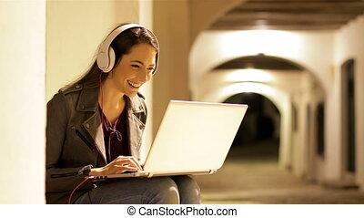 Happy woman using a laptop with headphones in the night -...