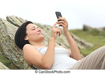 Happy woman using a mobile phone lying in the mountain