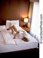 Happy woman using a mobile phone lying on the bed