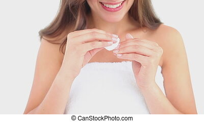 Happy woman using a nail polish remover against a white...