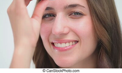 Happy woman using a pair of tweezers
