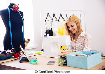 Happy woman using a sewing machine
