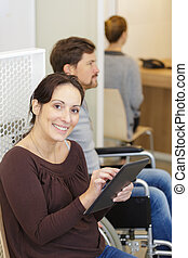 happy woman using a tablet in hospital