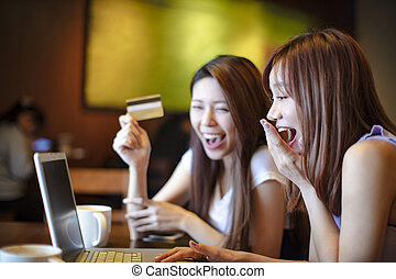 happy woman using credit card and laptop for online shopping