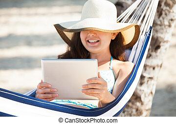 Happy Woman Using Digital Tablet In Hammock