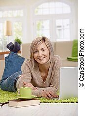 Happy woman using laptop at home
