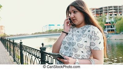 Happy woman using smartphone and tablet pc in the park