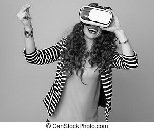 happy woman using virtual reality gear and snapping fingers