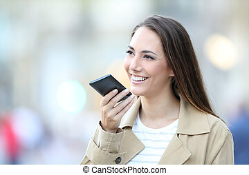 Happy woman using voice recognition on cell phone