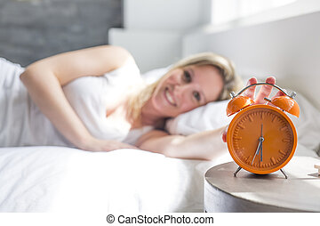 Happy woman waking up and turning off the alarm clock having...