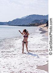 Happy woman walking along the shoreline