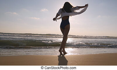 Happy woman walking and spinning on the beach near the ocean. Young beautiful girl enjoying life and having fun at sea shore. Su