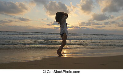 Happy woman walking and spinning on the beach near the ocean. Young beautiful girl enjoying life and having fun at sea shore. Summer vacation or holiday. Sunset landscape at background Close up