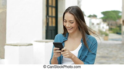 Happy woman walking and texting on cellphone in a street