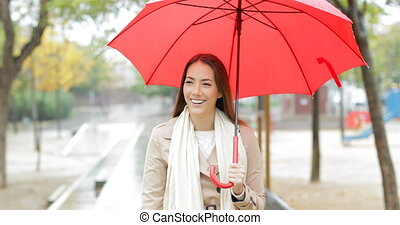 Happy woman walking holding an umbrella under the rain -...