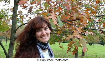 Happy woman walking in autumn park