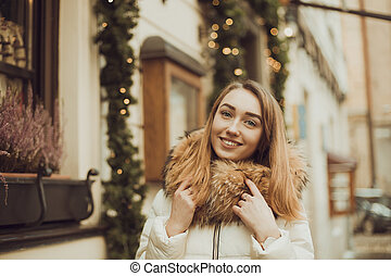 Happy woman walking in city, beautifully decorated for the Christmas